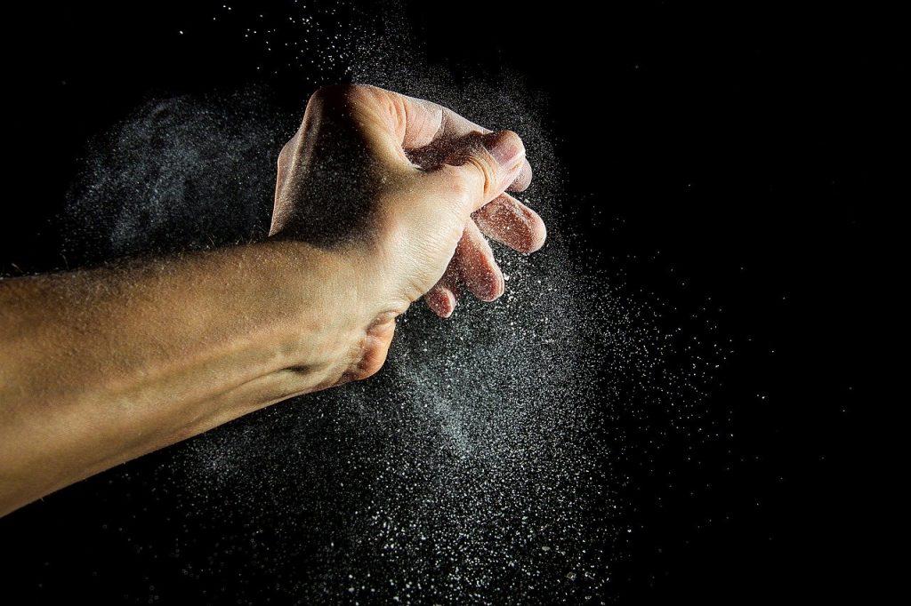 une main émiette de la levure
